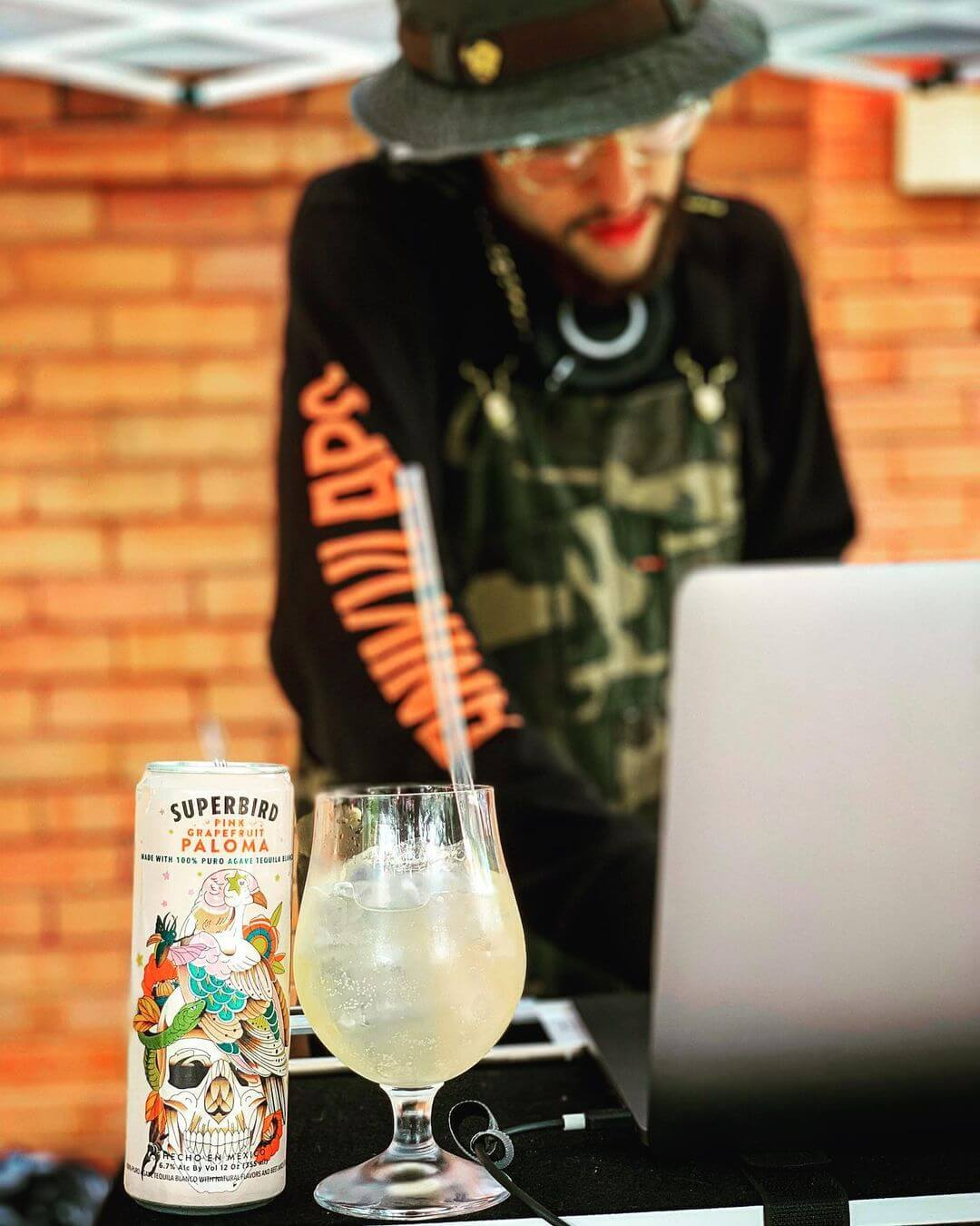 A man DJing behind a laptop with a glass of Superbird Paloma in front of him.