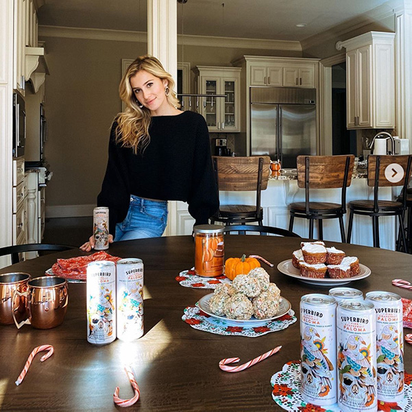 A woman standing behind a dining table with candy canes, popcorn balls, pumpkins, Superbird Palomas and other fall and winter objects on it.