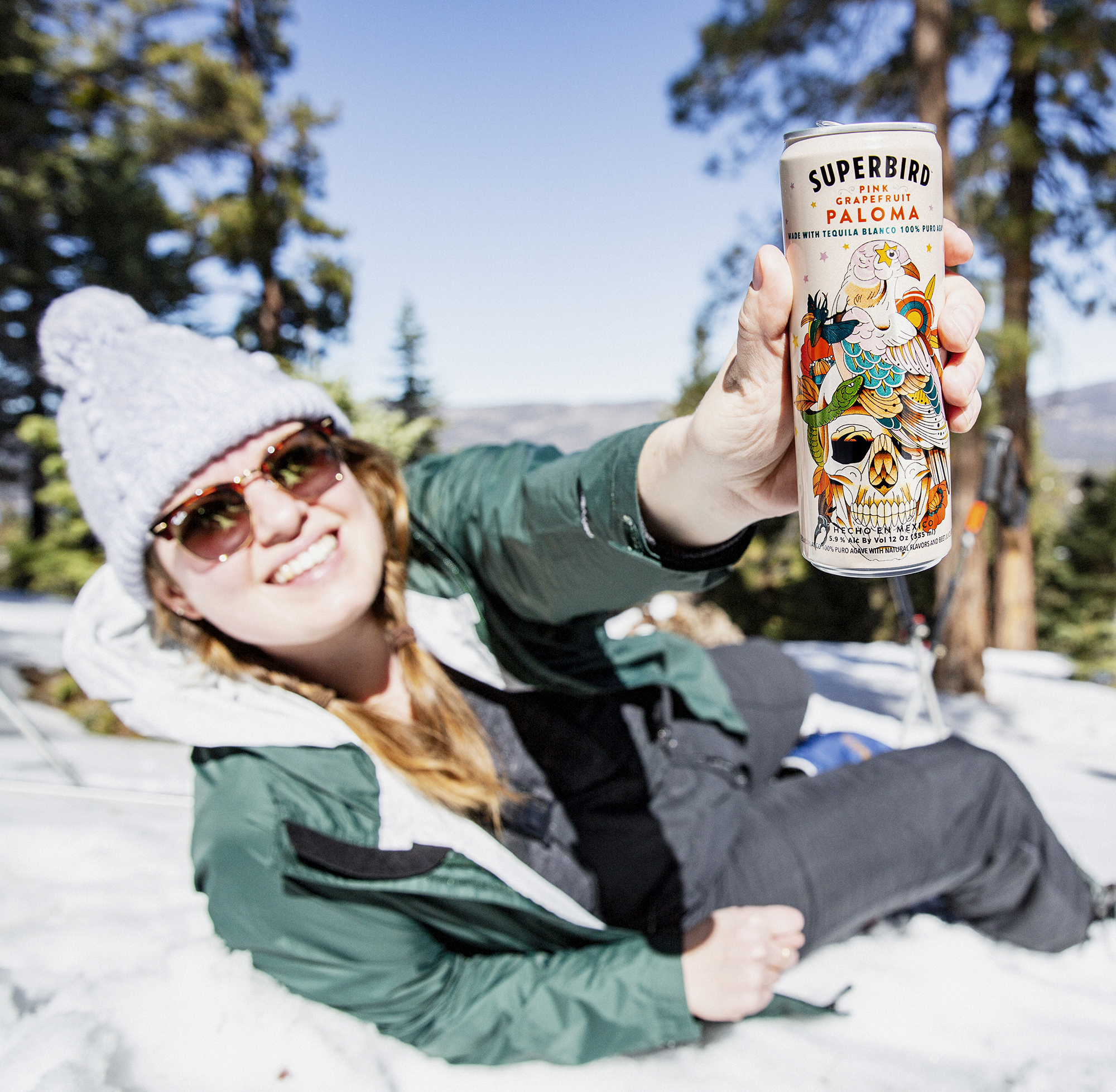 A snowboarder in full gear laying in the snow, showing a can of Superbird Paloma