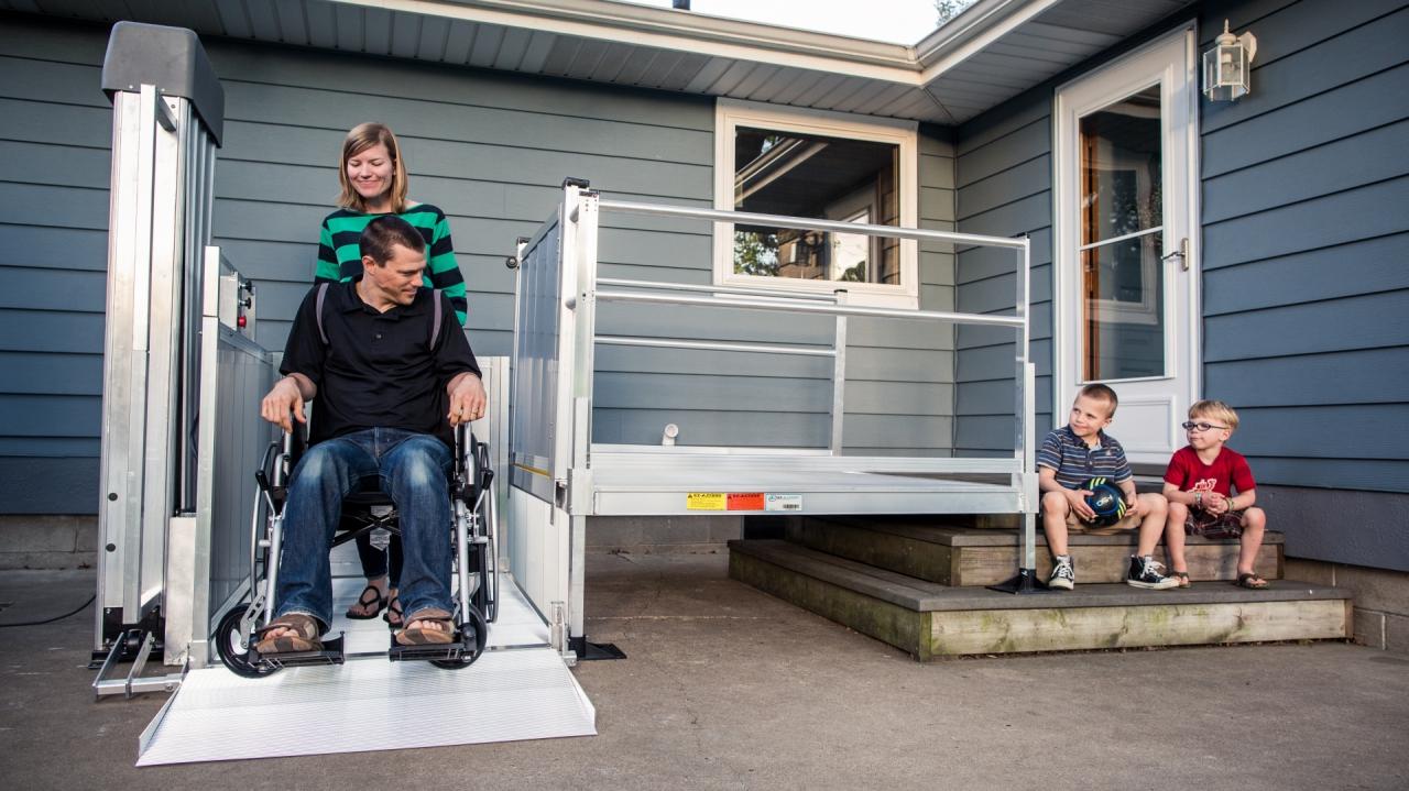 Woman helping a man in a wheelchair onto the PASSPORT Vertical Platform Lift