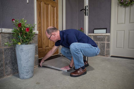 image of man placing a threshold ramp in front of his door