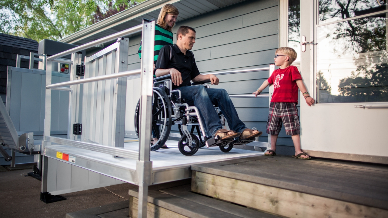 PASSPORT Vertical Platform Lift outdoors with a wife helping her husband in his wheelchair with a child opening the door for them