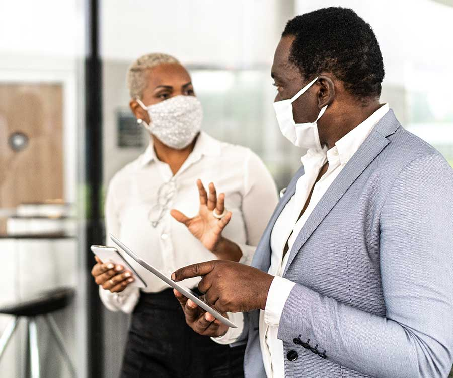 Two adults with masks on conversing about information displaying on their smart devices