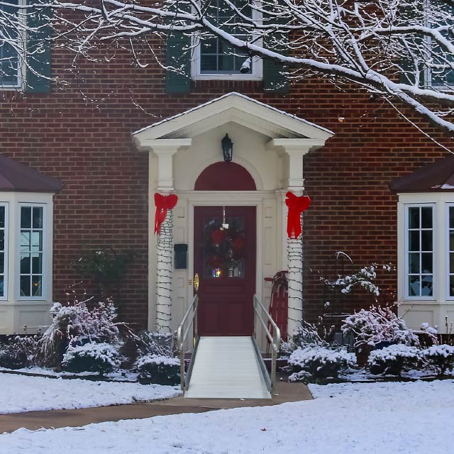 semi-portable ramp at the entrance of a home decorated for the holidays with snow on the ground