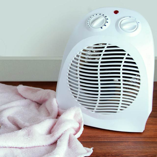space heater and blanket on a hardwood floor