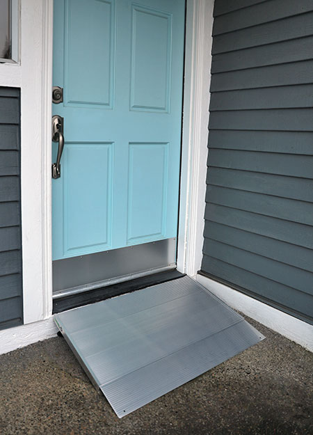 Blue home entry door with the Transitions angled entry ramp in front of it