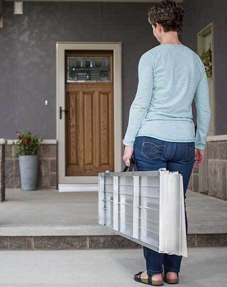 SUITCASE® Singlefold Ramp folded in two and being carried like luggage