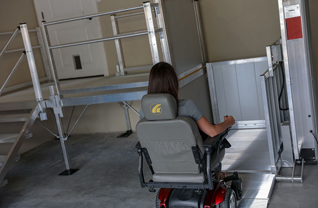 PASSPORT® Vertical Platform Lift in a garage with a woman on a motorized scooter driving into it