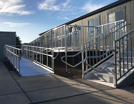 "TITANâ""¢ ramp system outside of portable school with both turn back system and stairs leading to entrance"