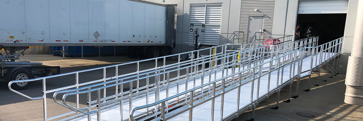 """two TITANâ""""¢ Modular Ramps extending out of loading dock zone to parking lot"""