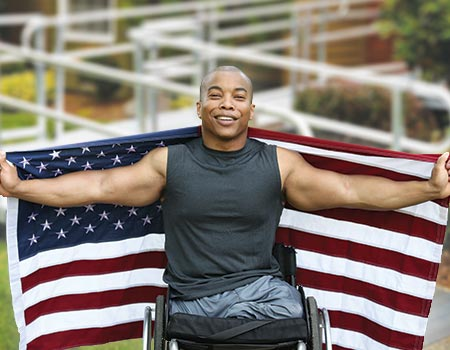 disabled veteran holding an American flag in front of home with modular ramp