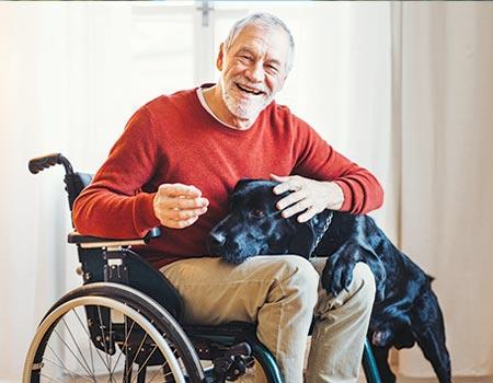 elderly man with black lab on lap inside home