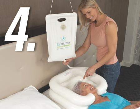 EZ-SHAMPOO® Hair Washing Basin and EZ-Shower being used on elderly woman with the help of an aid