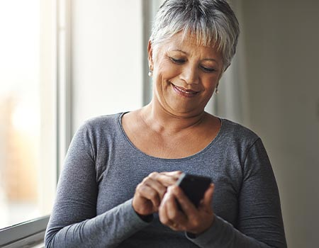 older woman looking at cell phone while dialing