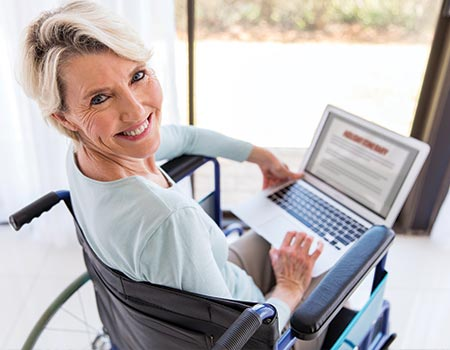 older woman in wheelchair looking at family itinerary on laptop
