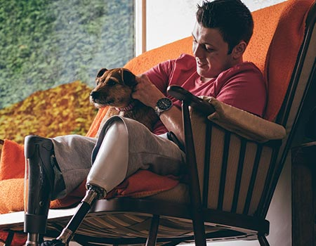 younger man sitting in chair with dog on lap