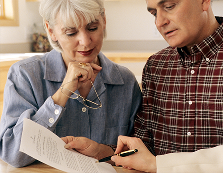elderly couple reviewing important paperwork with a concerned look on their face