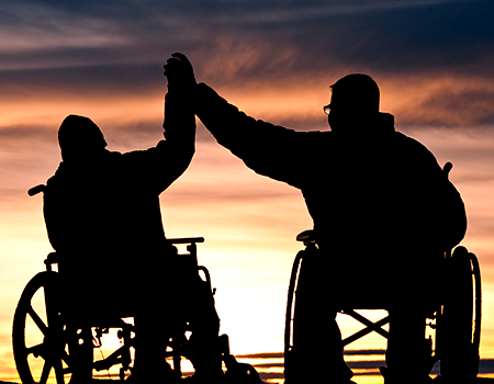 silhouette of two people in wheelchairs giving each other a hi-five with the sunset in the background