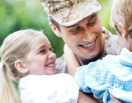 male veteran adult holding two children in his arms, all of them smiling
