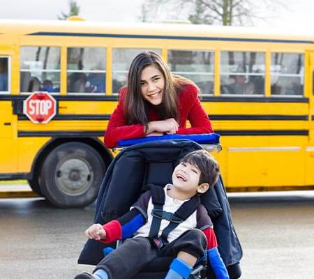 teenage girl in red jacket pushing younger boy in wheelchair beside a yellow school bus