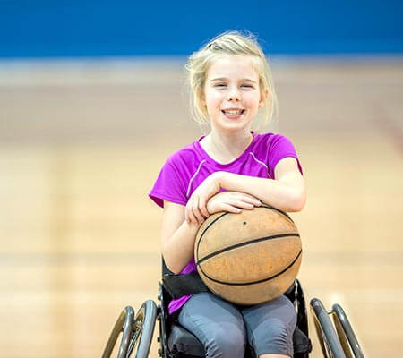 young blonde girl in school gym holding a basketball in a wheelchair