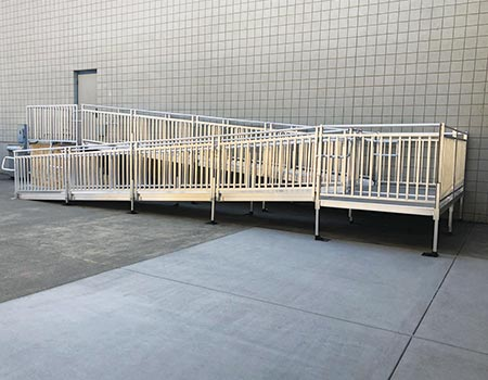 "TITANâ""¢ ramp system with turn back platform leading up to door at a school"