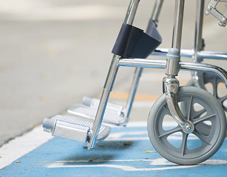 close up of wheelchair foot pedals and front wheels outside on concrete