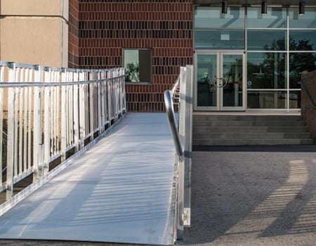 """TITANâ""""¢ ramp leading up to the front entrance of a school building"""