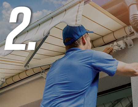 man installing an awning on a house