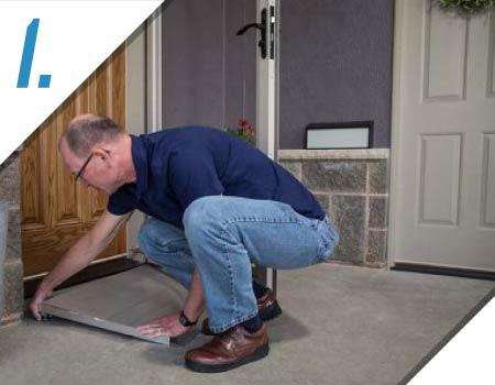 image of a man placing a door threshold ramp in front of a door