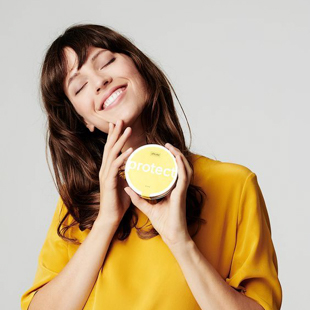 woman model holding a cylinder plastic package. One hand holds the package under her chin, the other hand is touching her face as she smiles teeth wide & eyes closed