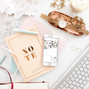 flat lay overhead shot of a notebook, iPhone, leather strapped watch, and assortment of office stationary supplies are spread across a desk