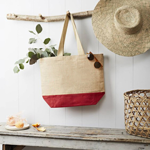 large over-the-shoulder purse is hanging off a branch with some leaves sticking out of the bag and a pair of sunglasses on the opposite side of the bag.