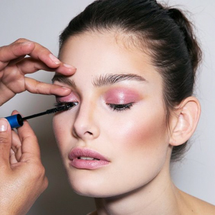 a woman makeup artist applys finishing touches of eye liner on another woman model who already has a fully designed face of professional makeup