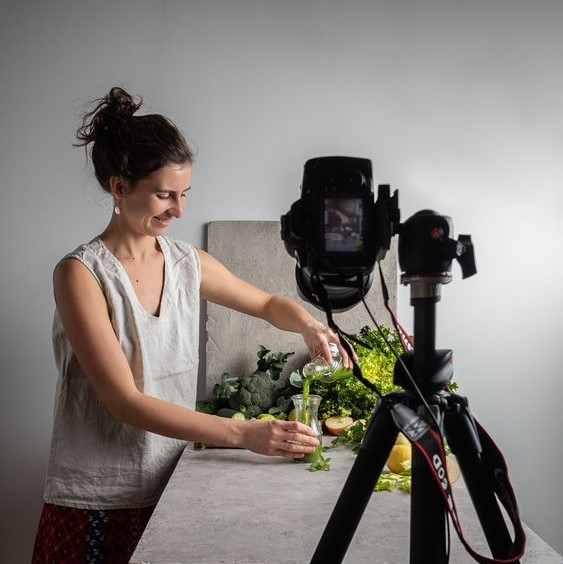 a camera is seen pointing towards a woman model whom is pouring vegetable juice into a cup. Various vegetables and healthy ingredients are behind the model.
