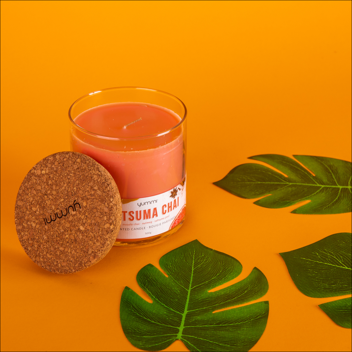 a scented candle seen from the side with a matching background and leaves used as props