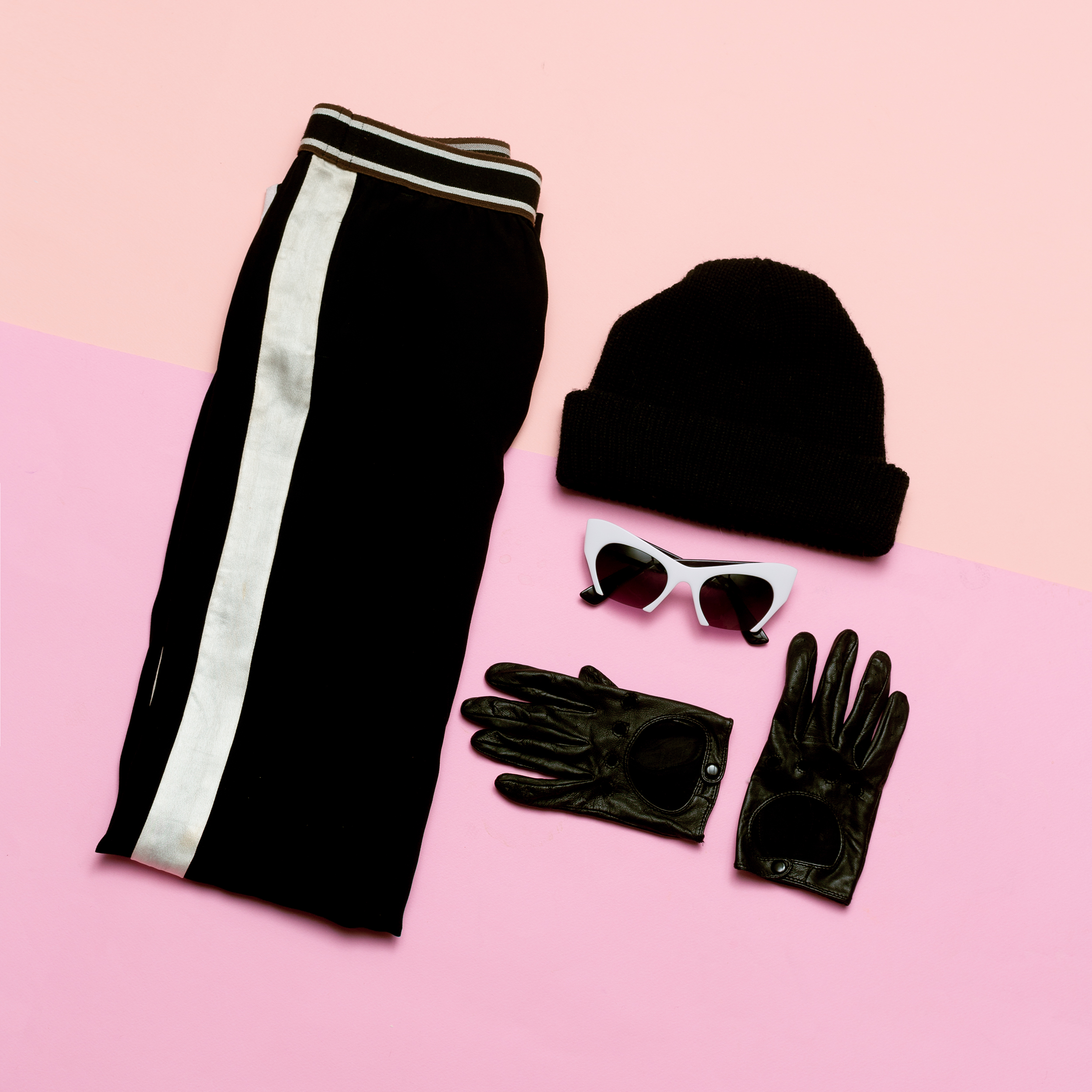black gloves, black snow hat, black track pants, and black/white sunglasses laying in a neat, folded arrangement