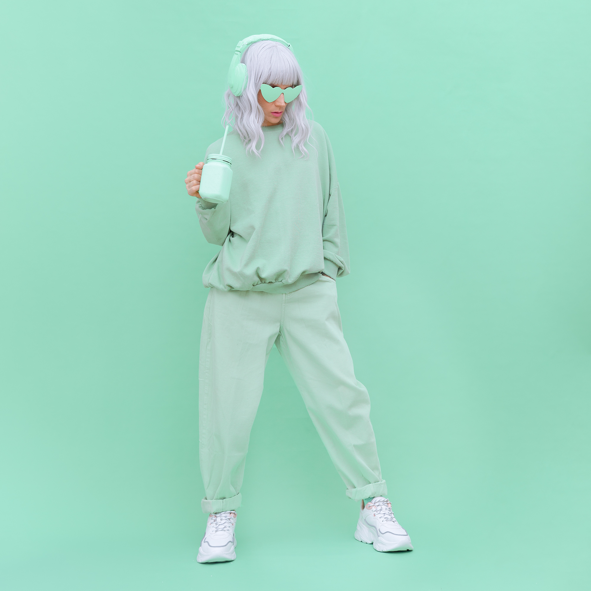 model wearing a track sweat suit and over-the-ear headphones while posing rhythmically standing up