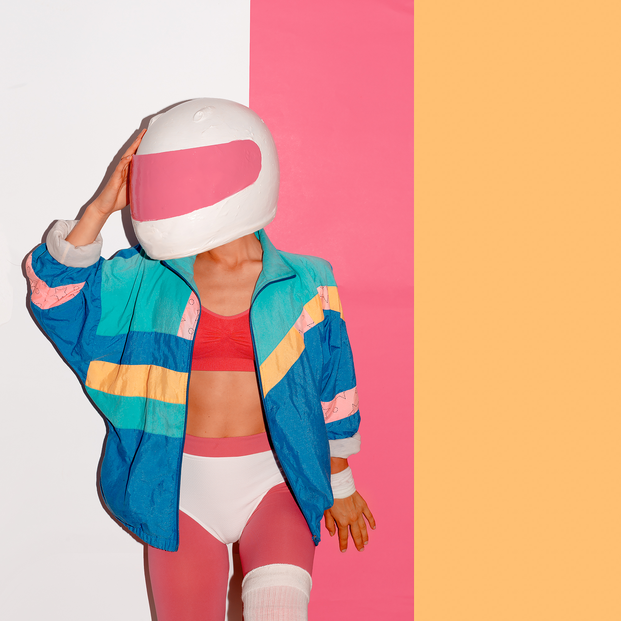 model wearing an astronaut helmet, jacket, and yoga outfit underneath