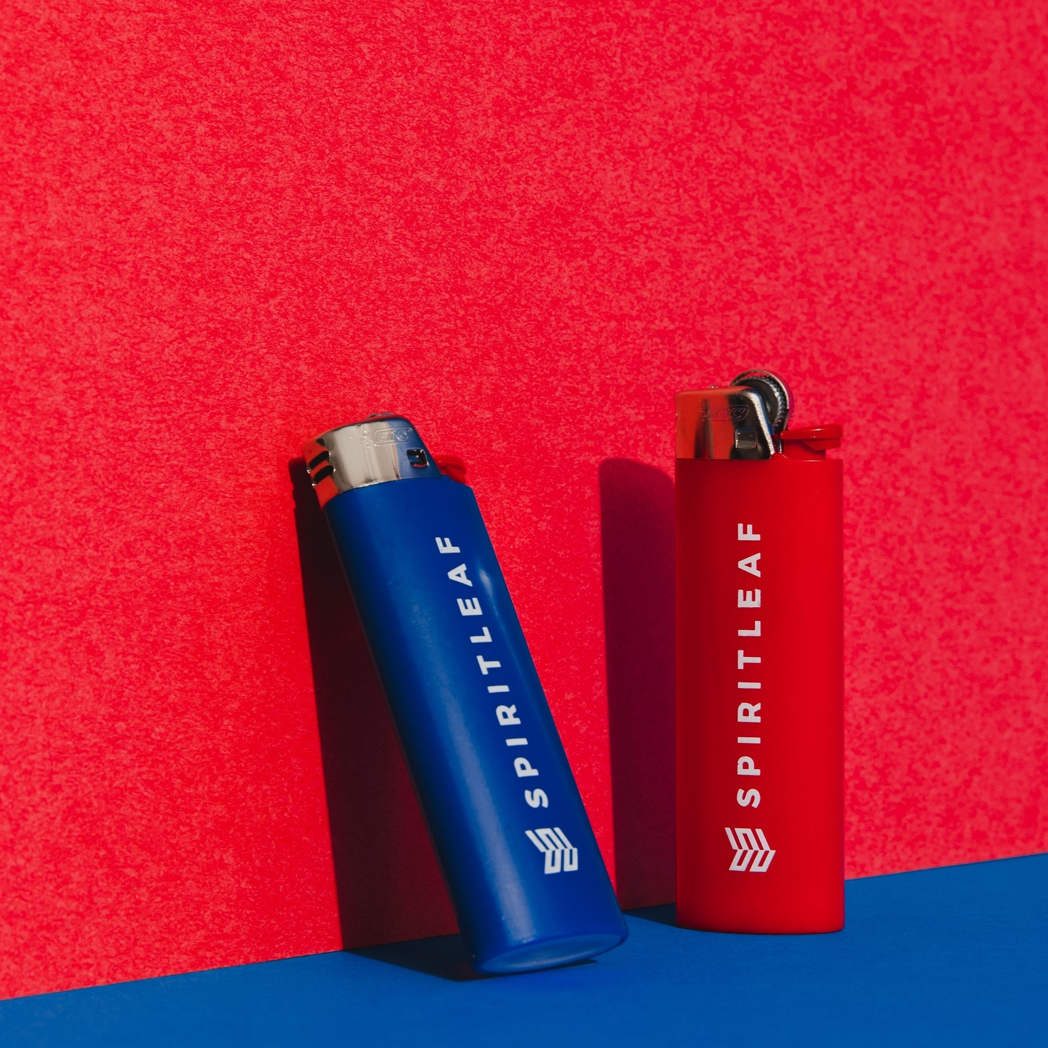 two lighters laying against a wall and standing vertically
