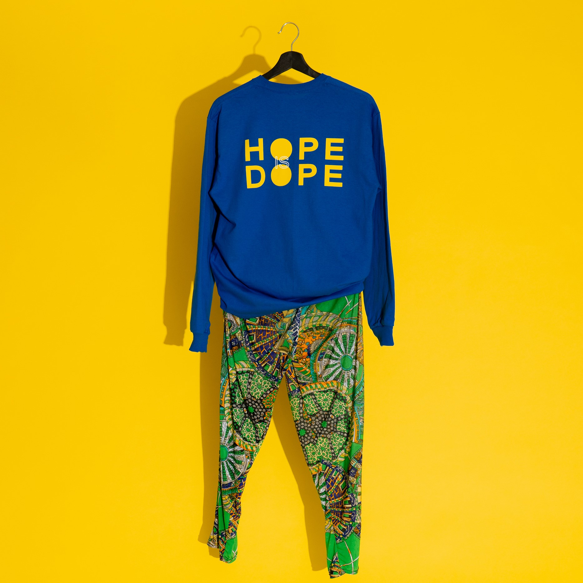 long sleeve sweatshirt that reads HOPEDOPE on the chest with baggy hippy pants all outfit hanging from a coat hanger