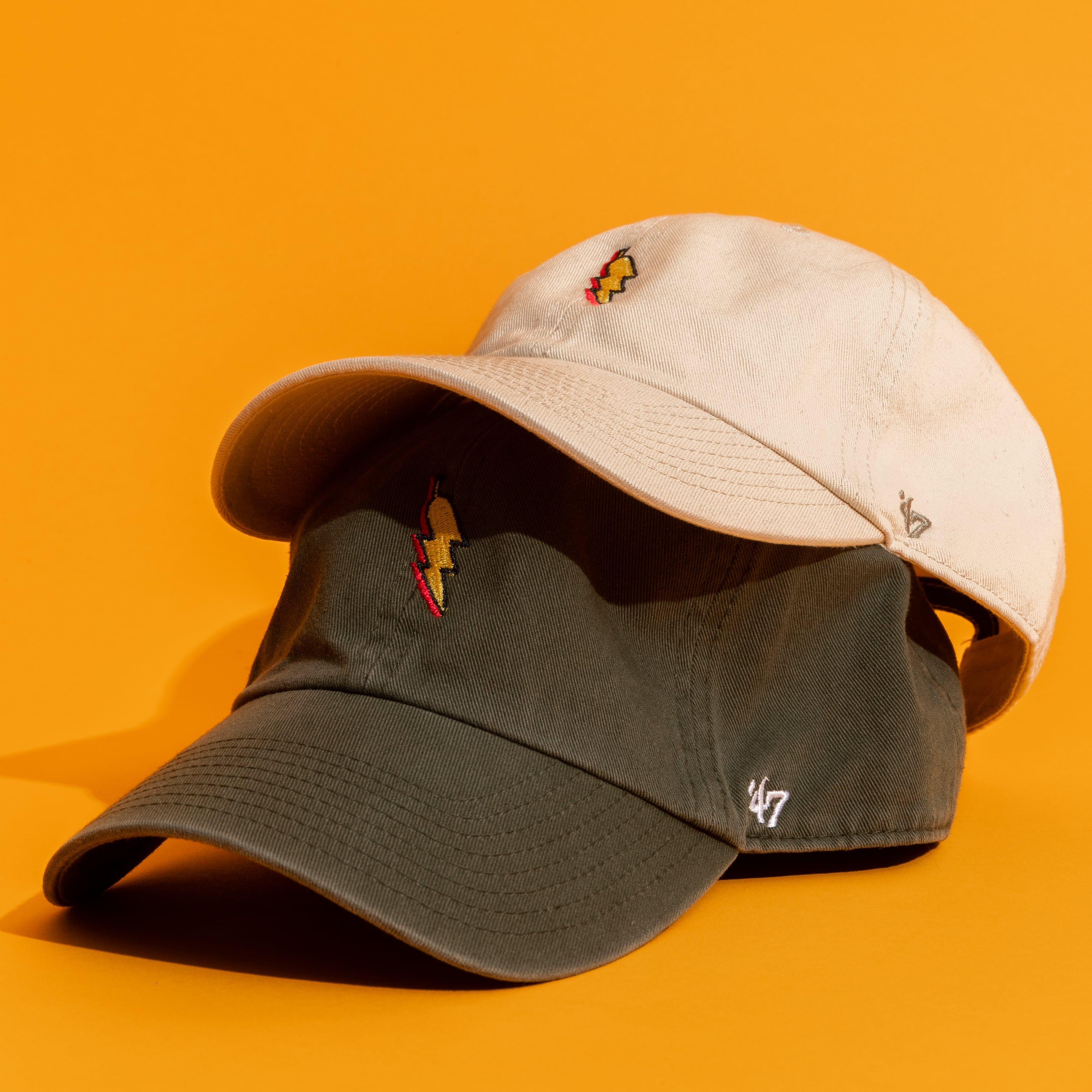 Two golf caps, one stacked on top of another but stacked slightly tilted-back to show the front side of both hats