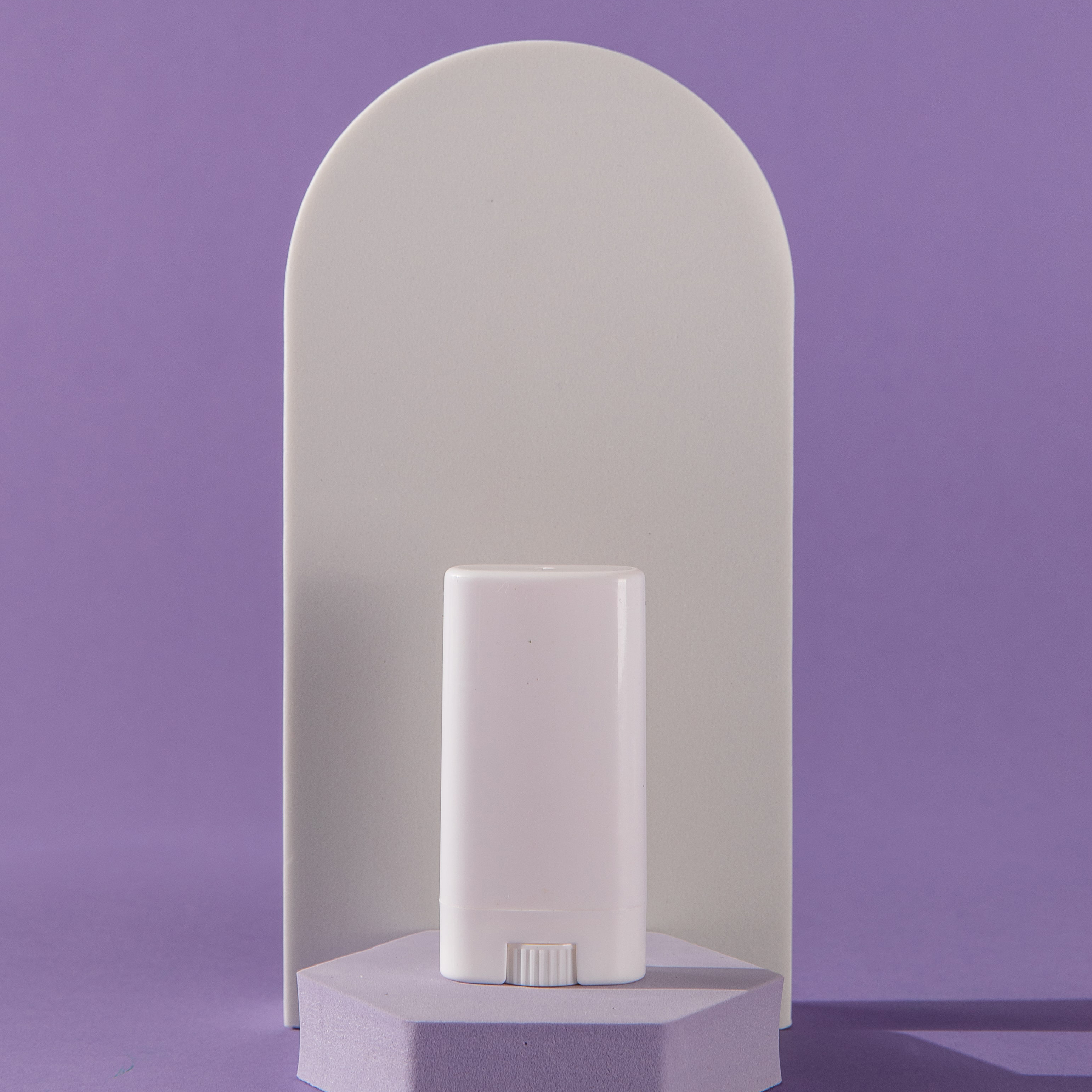 plain stick of deodorant on top of a small stand and all underneath an arch background