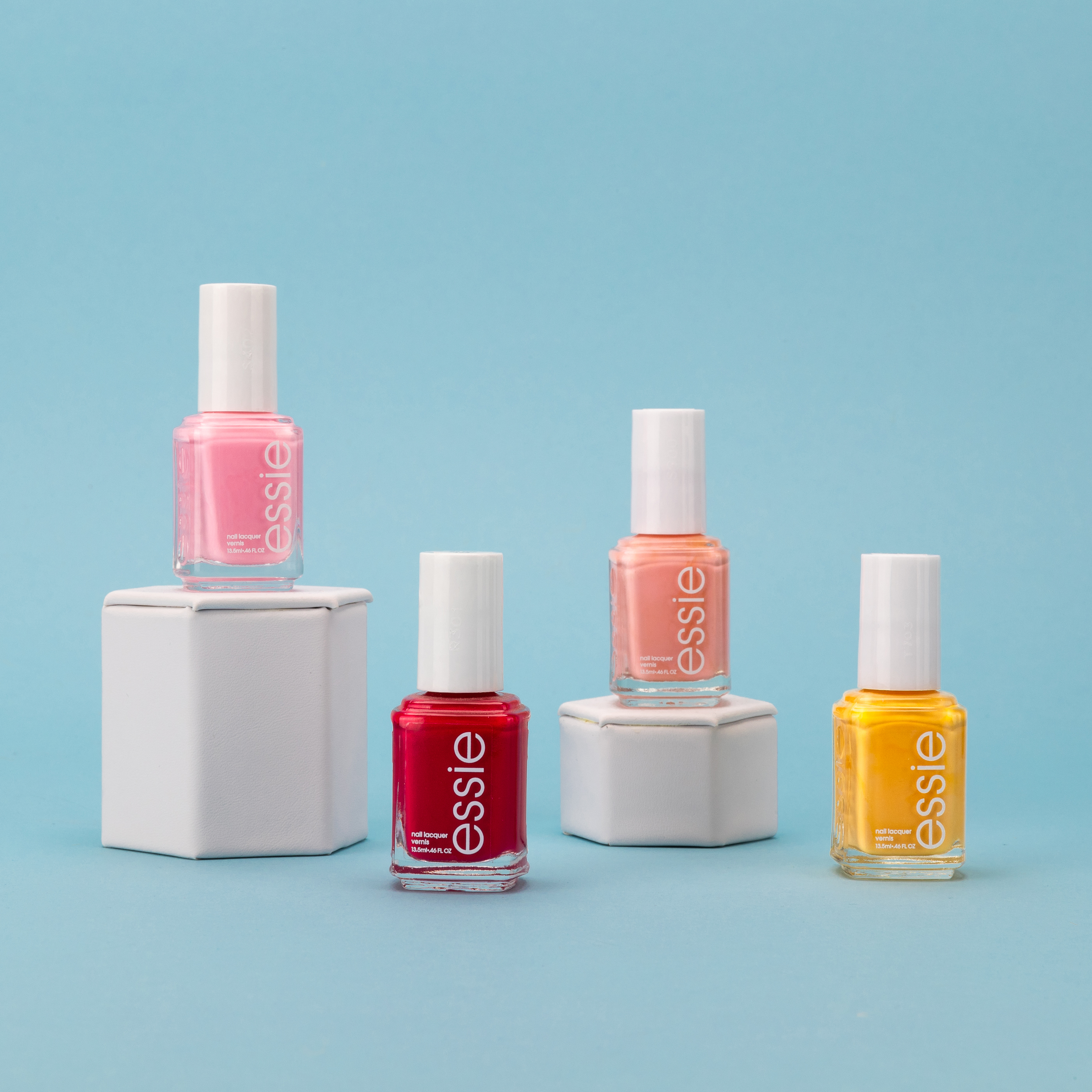 four small bottles of nail polish. the first and third are standing on taller podiums whereas the second and last ones are standing upright on the floor.