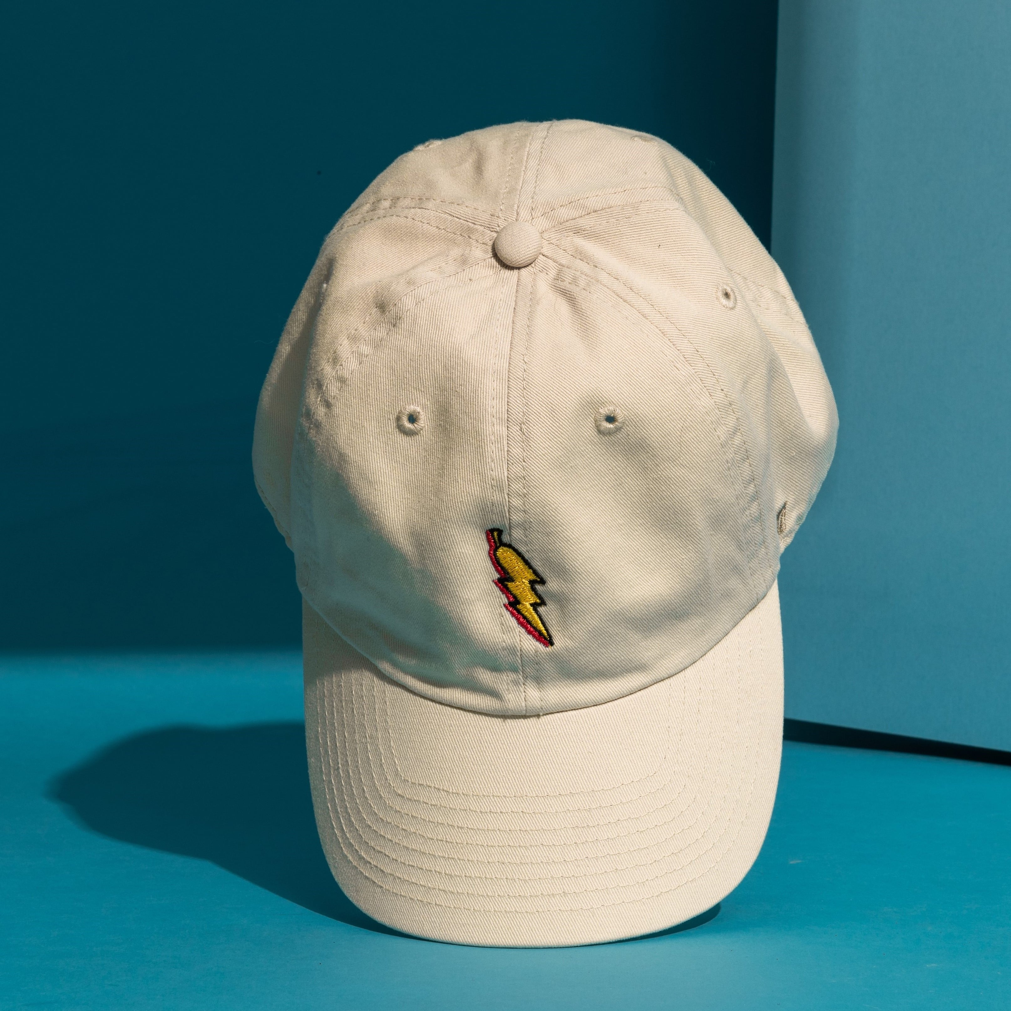 grandpa baseball cap shown standing on the bill of the cap showing it's lightning bolt logo on the front