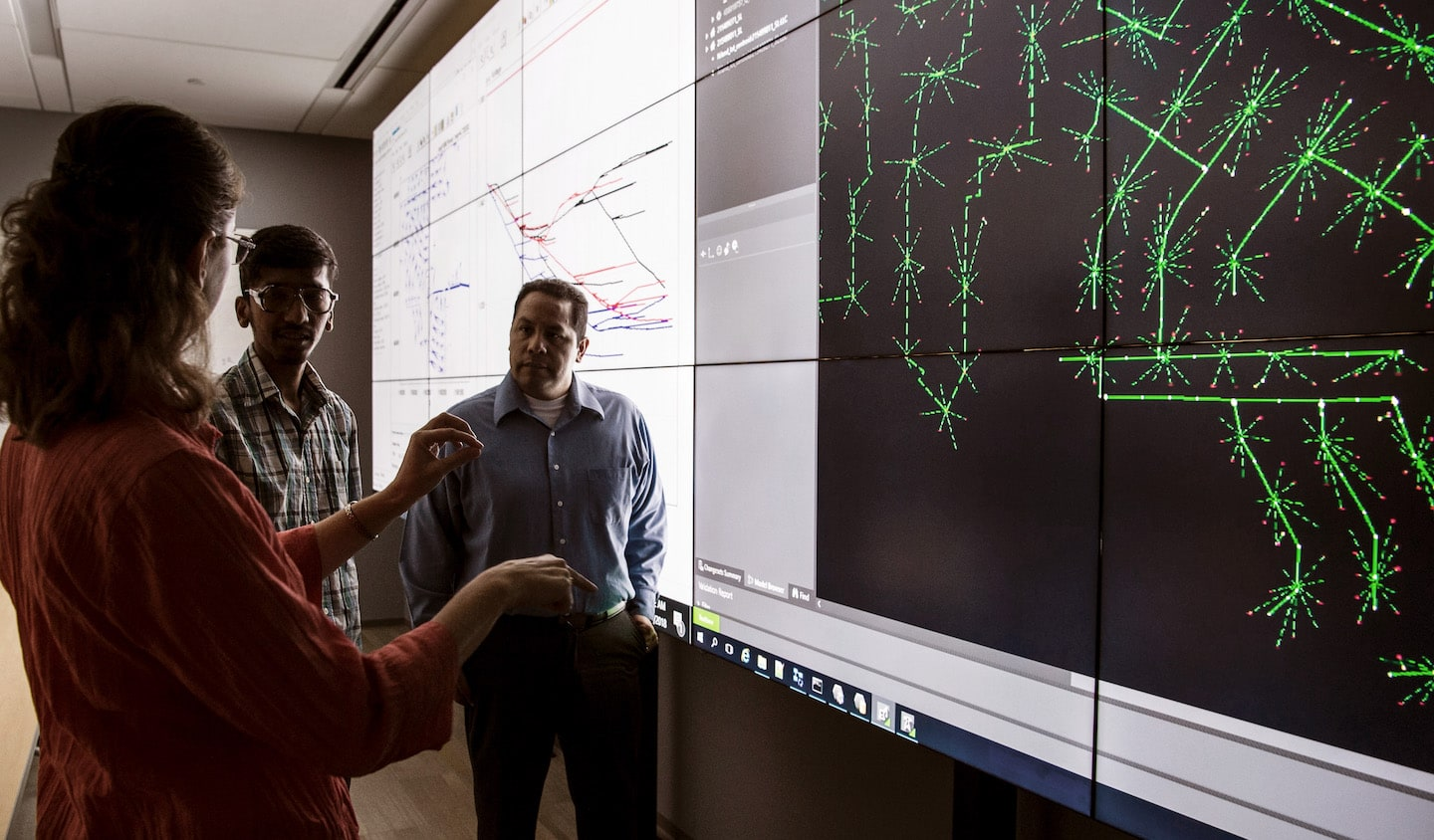 Two people discussing science in front of a screen