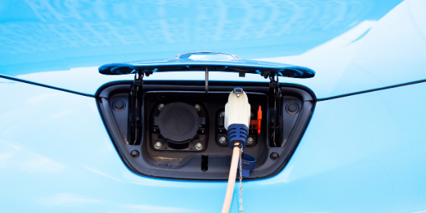 An EV charger plug inserted into a blue, light-duty electric vehicle for charging.