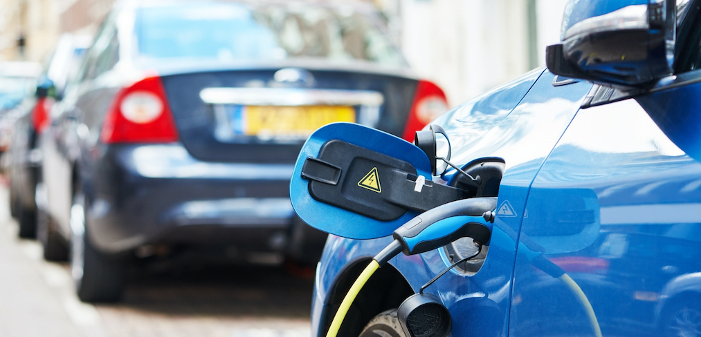 An EV charger plugged into a blue electric car, charging the vehicle's battery.