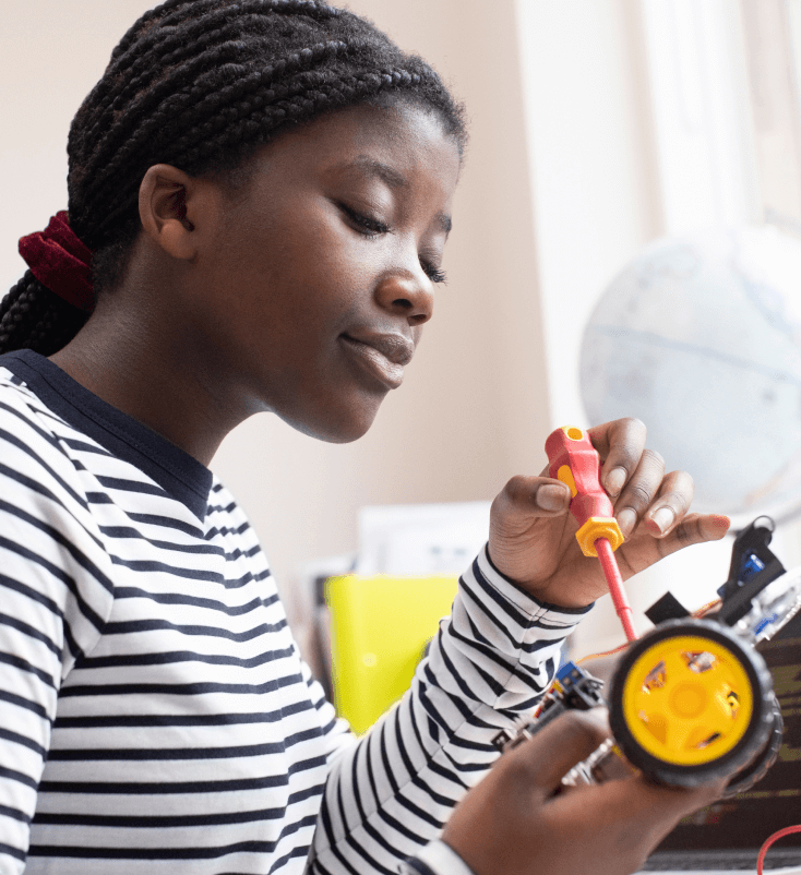 A female middle school student working on robotics.