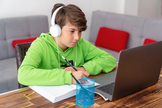 A middle school boy remote learning with his laptop and headphones.